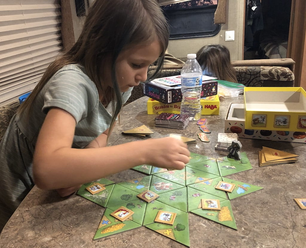A girl staring down at a gameboard. Her hand is blurry, placing a piece down on the table.