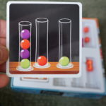 Dr. Eureka card showing three test tubes with colored balls